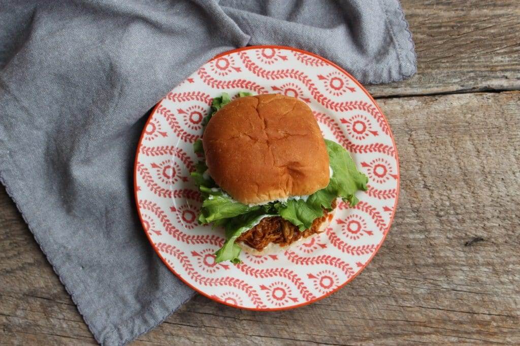 Barn wood board with a floral patterned orange and white plate and blue cloth napkin on with a shredded chicken, French onion sandwich on a white bread hamburger bun with mayo and green, leafy lettuce.