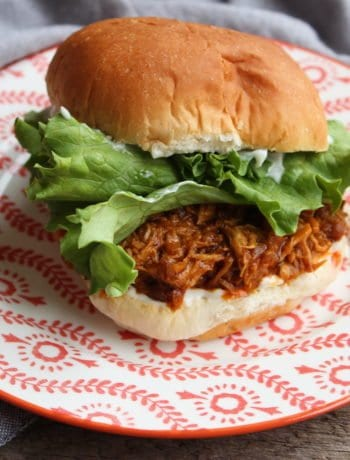 Barn wood board with a floral patterned orange and white plate and blue cloth napkin on with a shredded chicken, French onion sandwich on a sweet Hawaiian bun with mayo and green, leafy lettuce.