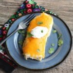 A blue plate with a large burrito on it with cheddar cheese melted on top. A multi colored floral towel is beside the plate and the plate sits on two wooden planks.