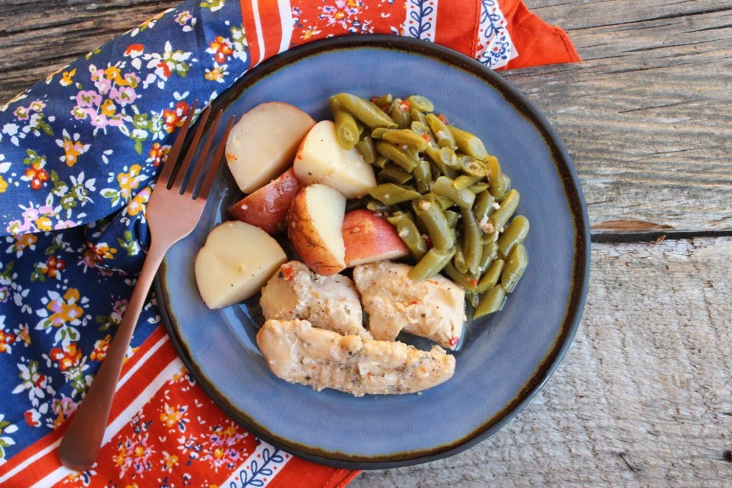 A blue, glass plate on a barn wood back drop with a floral, multi-colored linen beside the plate and a bronze colored fork beside the plate. Three chicken tenders, cut green beans, and large chunks of sliced red potatoes with Italian Marinade dressing over the top of all of the food is on the plate.