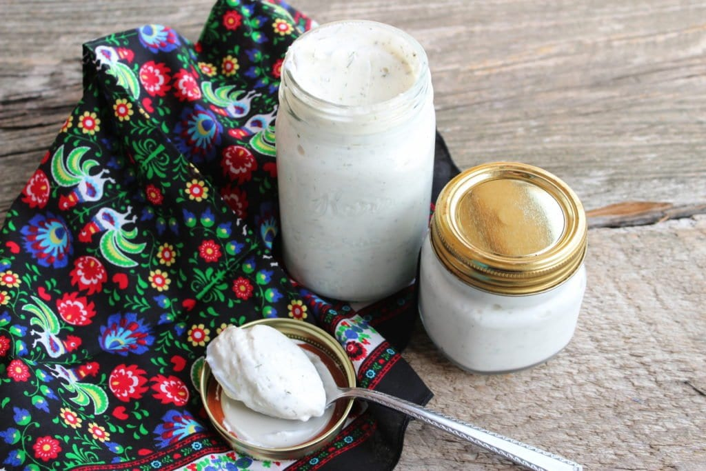 Two Kerr clear glass canning jars with gold lids and white, ranch salad dressing inside. Jars are on a barn wood board back drop with a floral, multi colored towel. A silver spoon with ranch dressing in the spoon sits on the open lid of the largest Kerr jar.