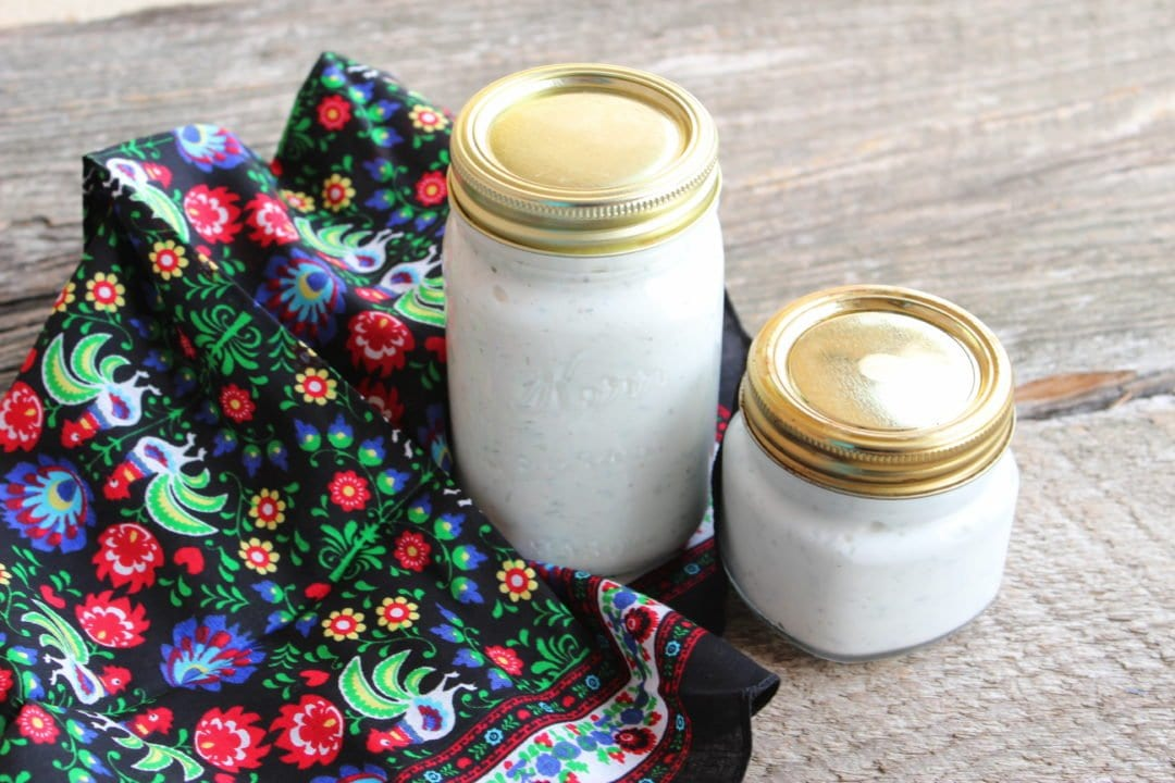 Two Kerr canning jars with gold lids filled with homemade ranch dressing. Jars are on a barn wood back drop with a floral, multi-colored linen to the left of the jars.