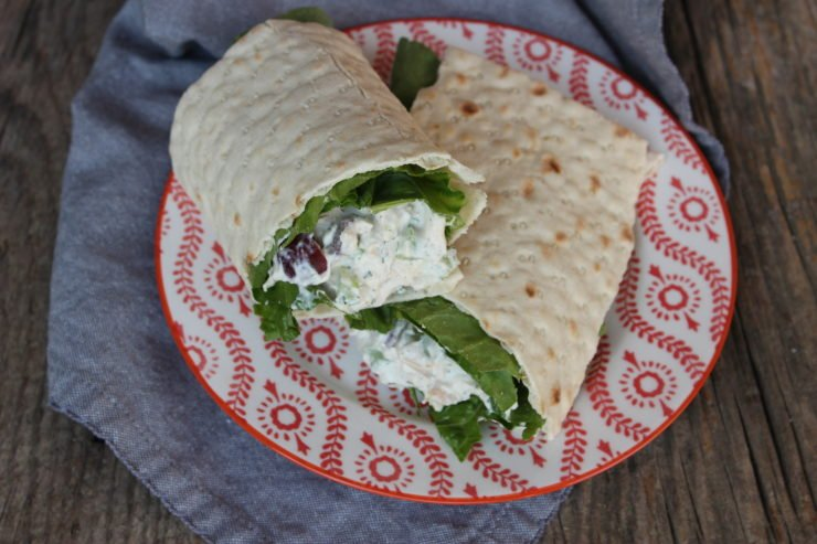 Southern Style Chunky Chicken Salad with leaf lettuce on a Lavash bread wrap. The Chicken Salad Wrap is on a coral and white floral plate with a blue towel under the plate. The plate and towel are sitting on two board planks.
