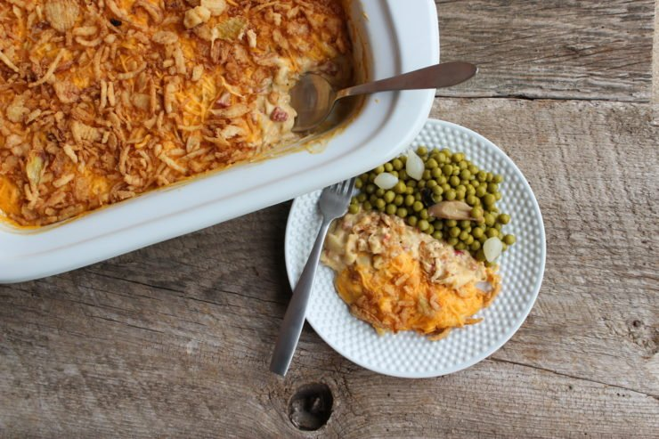 White Crockpot slow cooker casserole pan with creamy chicken macaroni casserole inside. The casserole is topped with melted cheddar cheese and french fried onions. A small, white plate with a silver fork is next to the casserole dish with the casserole and green peas on the plate. The casserole has a silver spoon inserted in one end of the casserole.