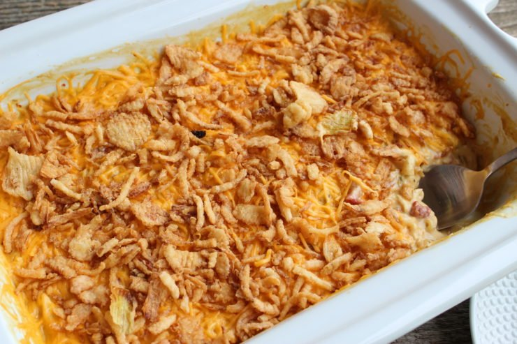 White Crockpot slow cooker casserole pan with creamy chicken macaroni casserole inside. The casserole is topped with melted cheddar cheese and french fried onions.