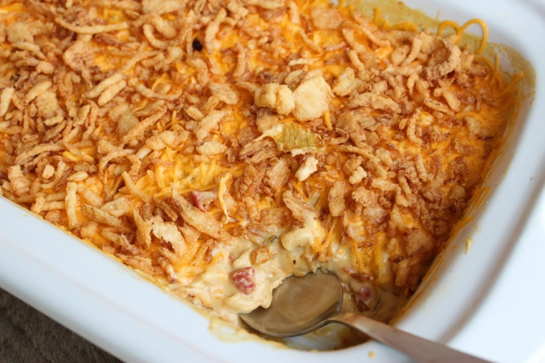 White Crockpot slow cooker casserole pan with creamy chicken macaroni casserole inside. The casserole is topped with melted cheddar cheese and french fried onions. The casserole has a silver spoon inserted in one end of the casserole.