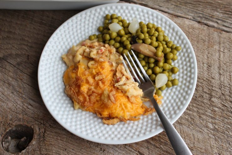White hobnail plate with Slow Cooker Creamy Chicken Macaroni Casserole and green peas with onion and mushroom and a silver fork on the plate. Plate is sitting on a barn wood back drop.