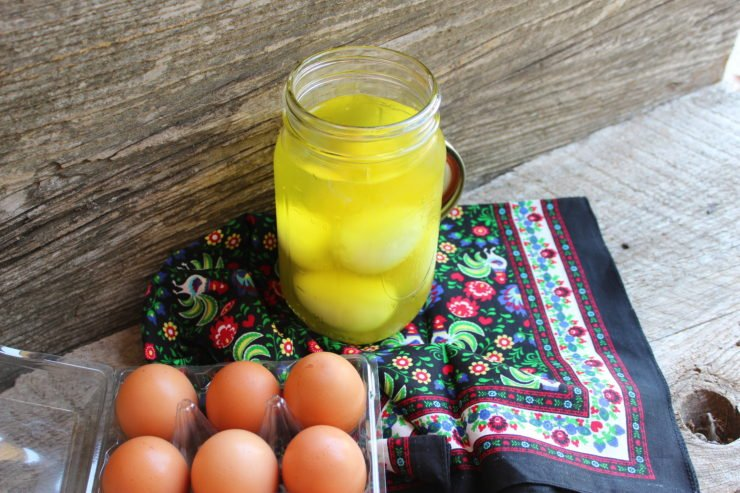 A wood backdrop with a large mouth, Ball Mason jar with pickle juice and six, peeled and cooked hard boiled eggs inside. A multi-colored, floral towel is below the jar. A dozen of brown eggs sit in a plastic egg carton next to the jar of pickled eggs.