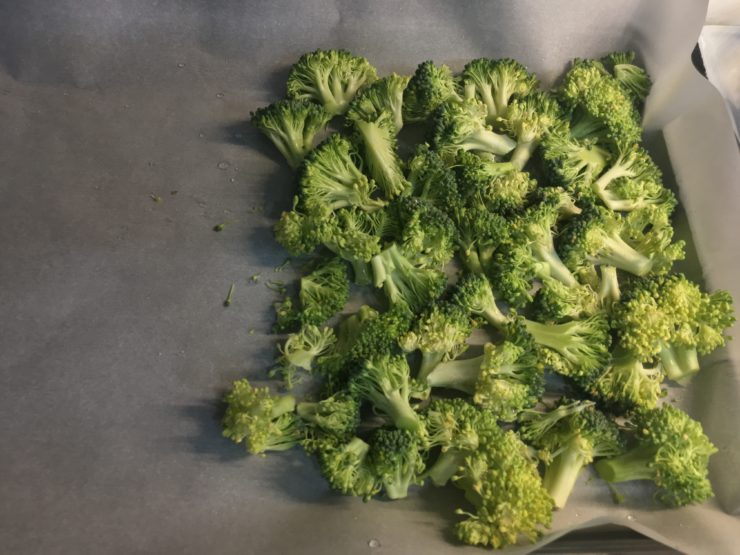 Chopped broccoli florets on a white, parchment paper that has been placed on a sheet pan.