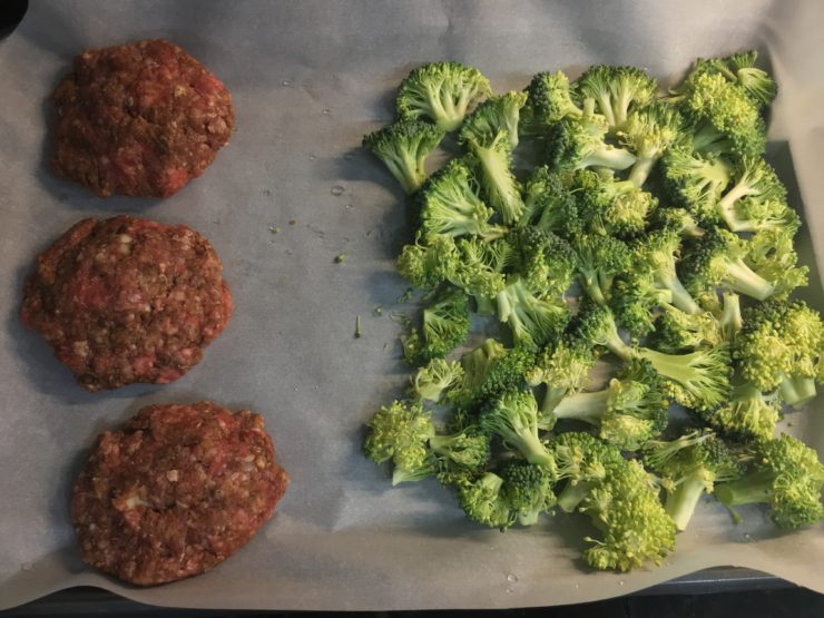 Three ground beef hamburger patties with a crown of broccoli chopped into florets on a sheet pan that is lined with parchment paper.