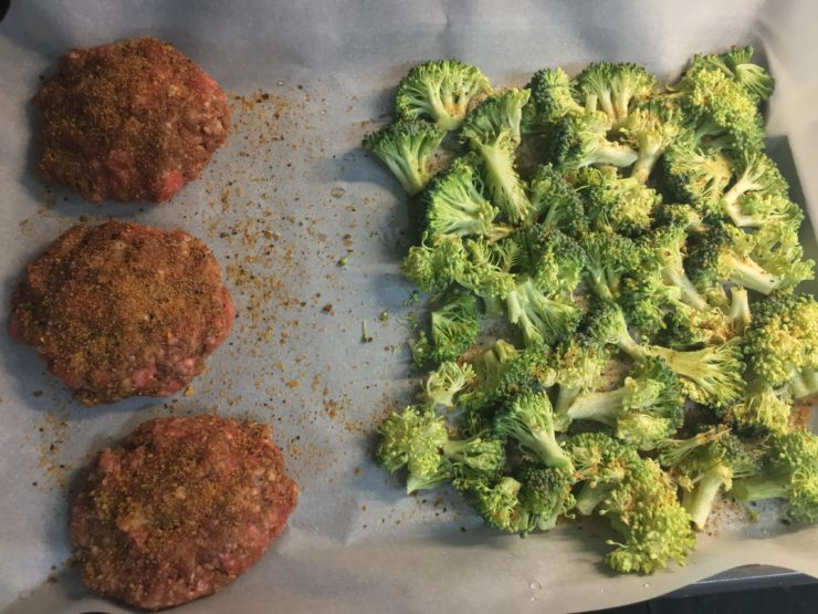 Three ground beef hamburger patties with a crown of broccoli chopped into florets on a sheet pan that is lined with parchment paper. Everything has been seasoned with a dry bbq rub.