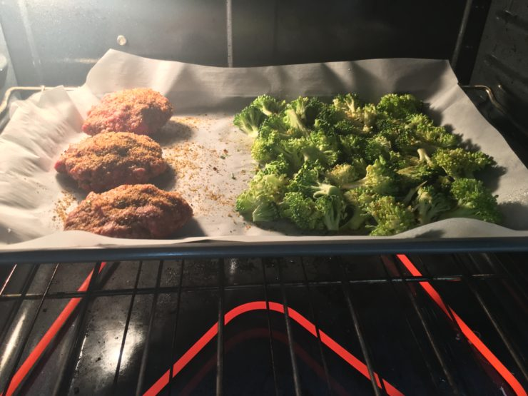 Three ground beef hamburger patties with a crown of broccoli chopped into florets on a sheet pan that is lined with parchment paper. Sheet pan has been placed in a pre-heated oven.