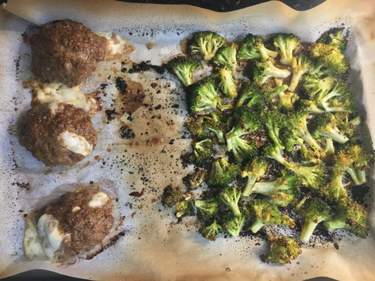 Three cooked and cheese stuffed beef hamburger patties with roasted broccoli florets on a sheet pan that has been lined with parchment paper.