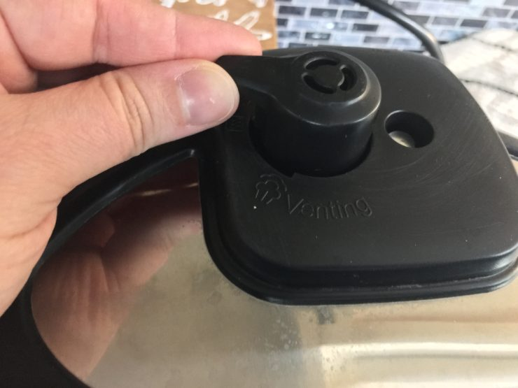 The lid and steam release valve of an Instant Pot Duo Pressure Cooker with a hand on the steam release valve.