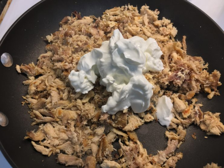 Large black skillet with shredded chicken, four ounces of cream cheese, and plain, nonfat Greek yogurt.