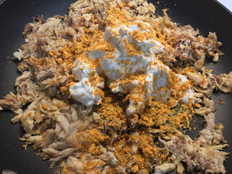 Large black skillet with shredded, cooked chicken, four ounces of cream cheese, plain, nonfat Greek yogurt, and taco seasoning.