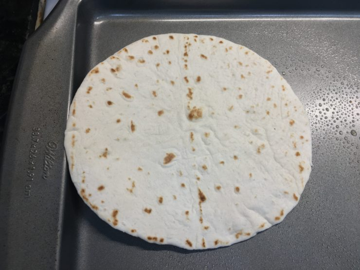 One flour, soft tortilla shell, taco sized, placed on a flat sheet pan.