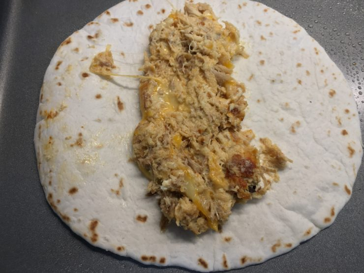 One small flour tortilla taco shell with the shredded chicken and cheese taquito mixture on a large sheet pan.