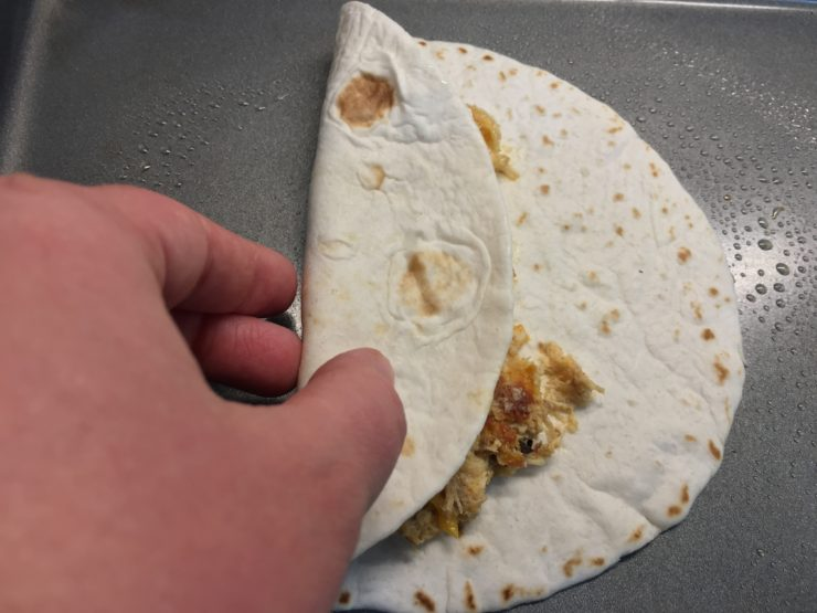 One flour tortilla folded in half with shredded chicken taquito mix inside, with a hand folding half of it over. Taquito is on a large, sheet pan.