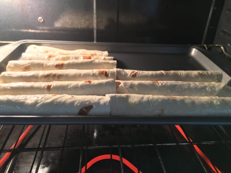 Large sheet pan with rows of uncooked flour tortilla chicken tortillas. Pan is in a heated oven.