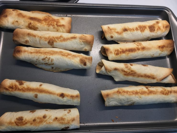 Large baking sheet with baked chicken taquitos in rows on the pan.