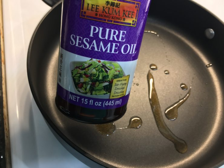 A large skillet with pure sesame oil inside the skillet and the bottle of sesame oil held beside the skillet.