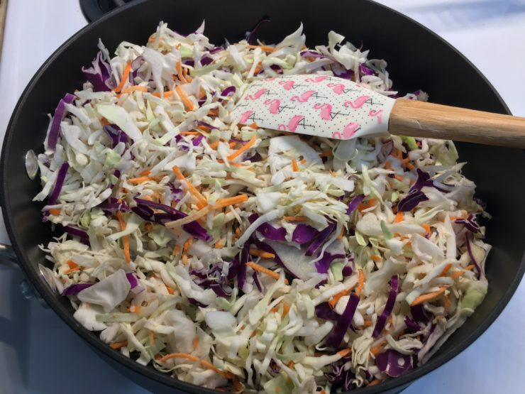 A large, black skillet with half of a bag of tri-colored coleslaw inside and a white spatula with pink flamingos in the pan.