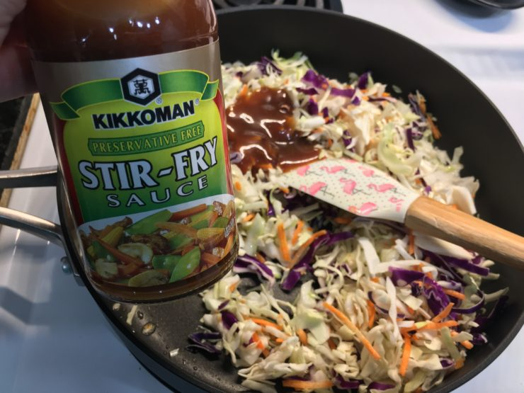 Large black skillet with tri colored coleslaw and one tablespoon of Stir Fry Sauce in the skillet.