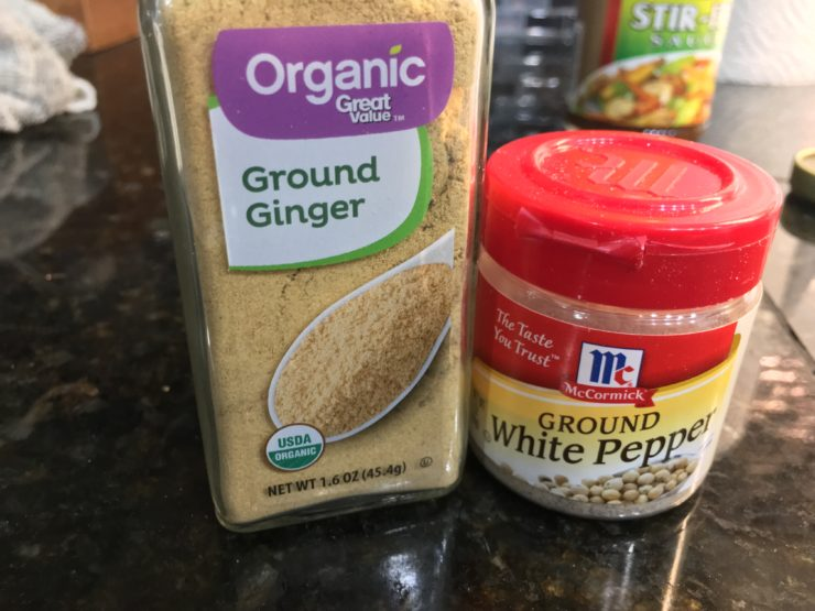 Organic ground ginger and ground white pepper on a black counter top.