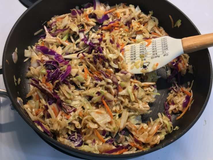 A large black skillet with tri colored coleslaw inside and Stir Fry Sauce that has been stirred into the coleslaw.