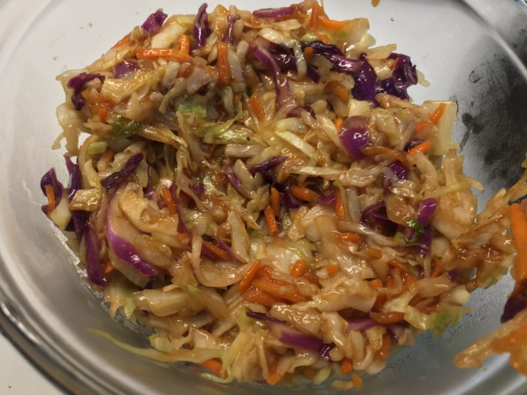 Cooked, tri colored coleslaw with stir fry sauce in a glass bowl.