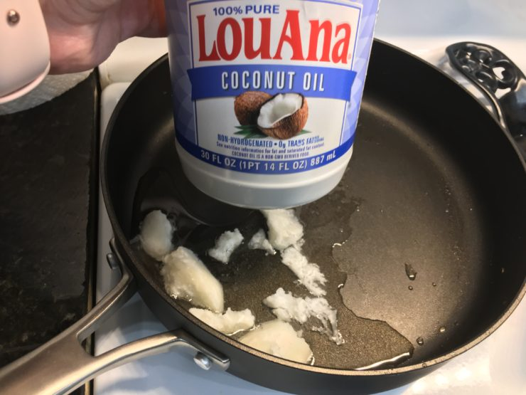 Large black skillet with Lou Ana coconut oil inside the skillet.
