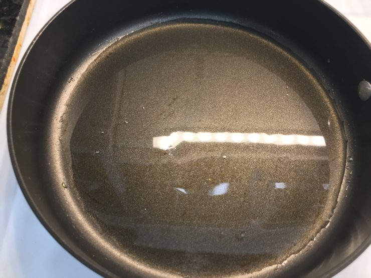 Large black skillet with melted coconut oil inside the skillet.