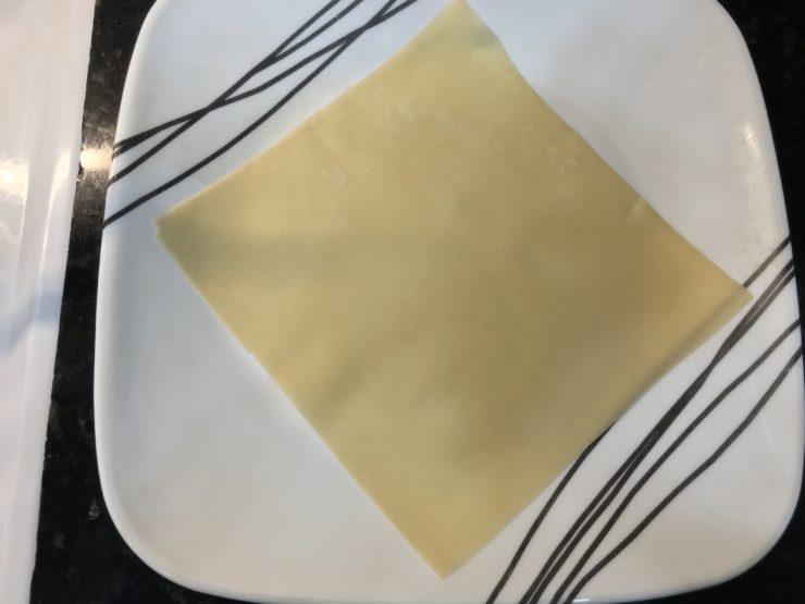 A white plate with black stripes and one egg roll wrapper placed on the plate, turned to look like a diamond.