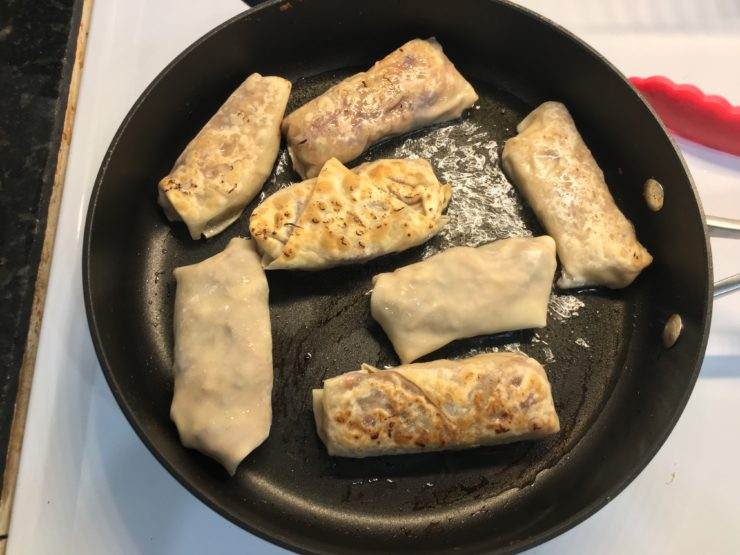 Large black skillet with melted coconut oil inside and seven, partially cooked egg rolls inside the skillet.