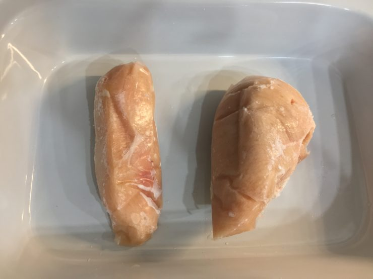 Two frozen, raw, boneless skinless chicken breast in a 9x13 Crockpot casserole slow cooker.