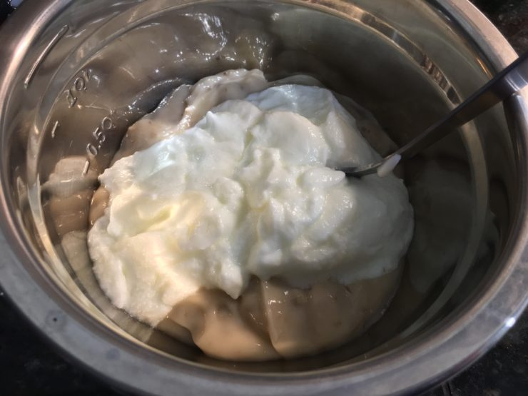 A silver mixing bowl with healthy cream of mushroom soup and one cup of plain, nonfat Greek yogurt inside.