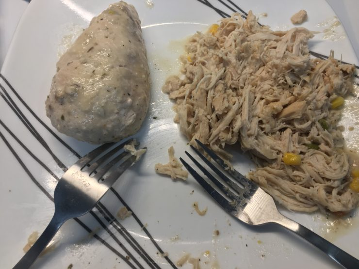 White plate with black stripes and cooked, shredded, boneless skinless chicken breast on the plate. Two silver forks are also on the plate.
