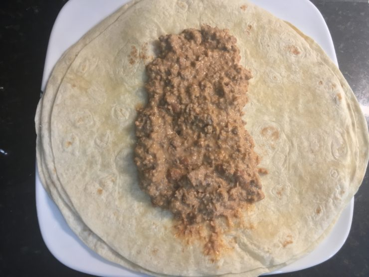White plate with a stack of flour, burrito tortillas and the beef and bean mixture in the middle of the burrito tortilla.