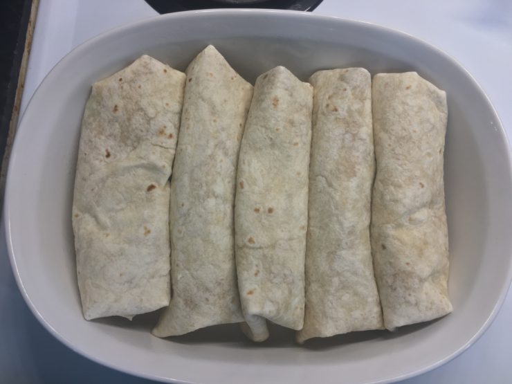 White casserole dish with five large burritos inside.