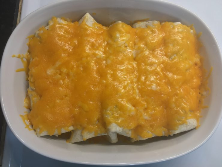 White casserole dish with baked burritos covered in cheese.