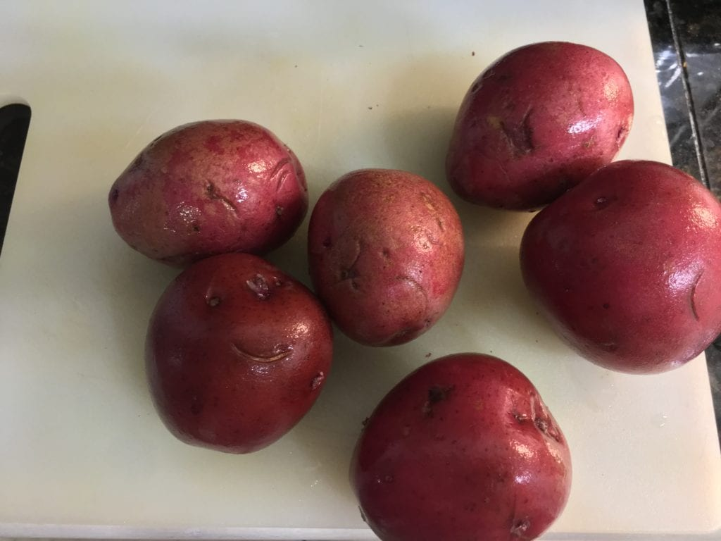 Six small, washed, red potatoes on a white cutting board.
