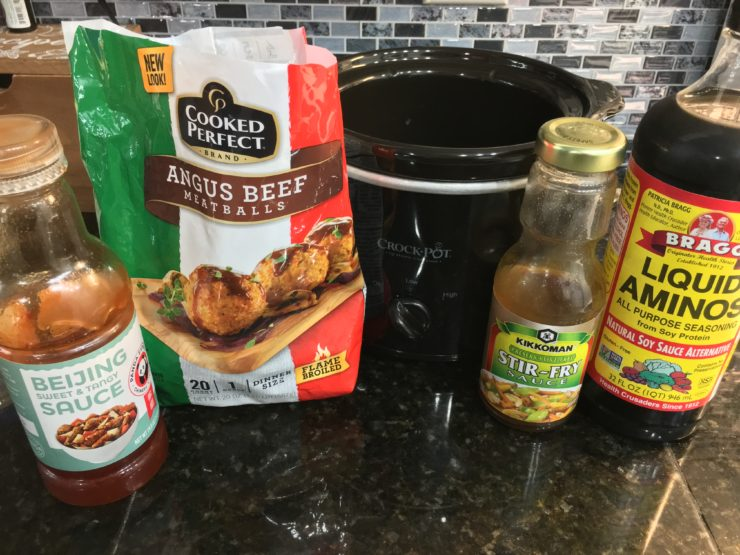Panda Express Beijing Sweet & Tangy Sauce, Angus Beef Meatballs, a two quart Crockpot slow cooker, Stir Fry Sauce, Liquid Aminos, all on a counter top.