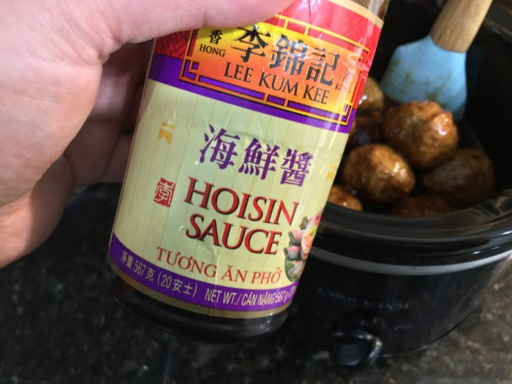 One bottle of Hoisin Sauce with crockpot full of frozen meatballs in the background.