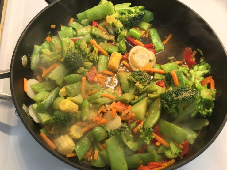 Large skillet with cooked stir fry in it, along with ground ginger and liquid aminos.