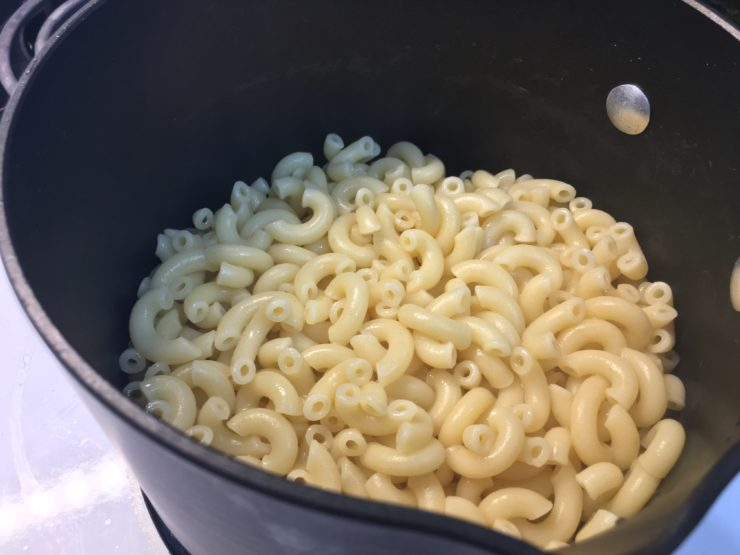 Black sauce pan with cooked, elbow macaroni noodles inside.