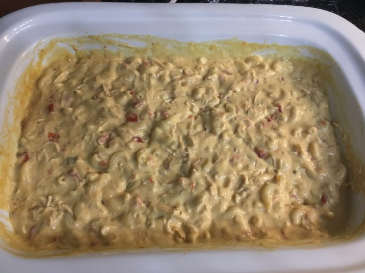 White casserole slow cooker with shredded chicken, macaroni noodles, mild tomatoes with green chilies, healthy cream of chicken soup, cream cheese, and onion soup mix inside.