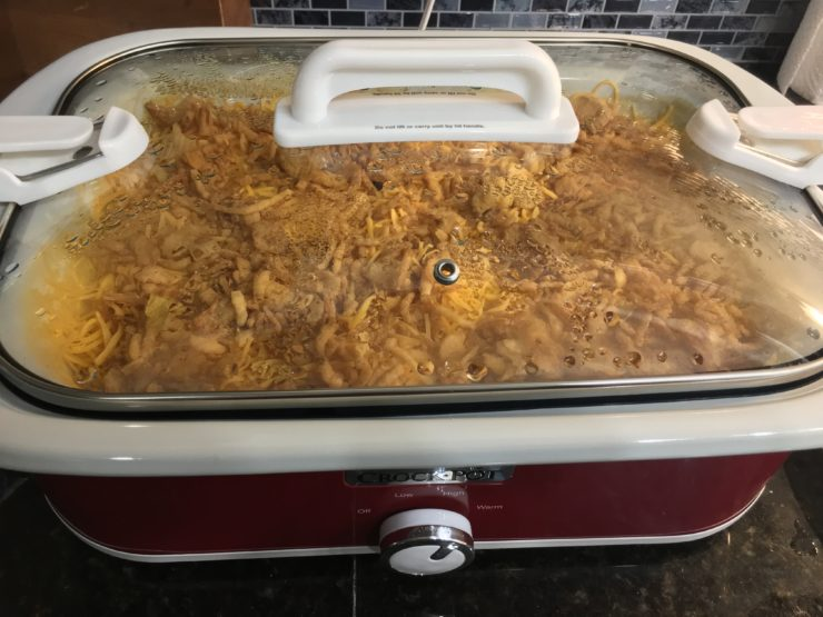 White casserole slow cooker with shredded chicken, macaroni noodles, mild tomatoes with green chilies, healthy cream of chicken soup, cream cheese, and onion soup mix inside. Casserole is topped with shredded, cheddar cheese and French fried onions. Lid is placed on the crockpot and crockpot is set to cook on high.