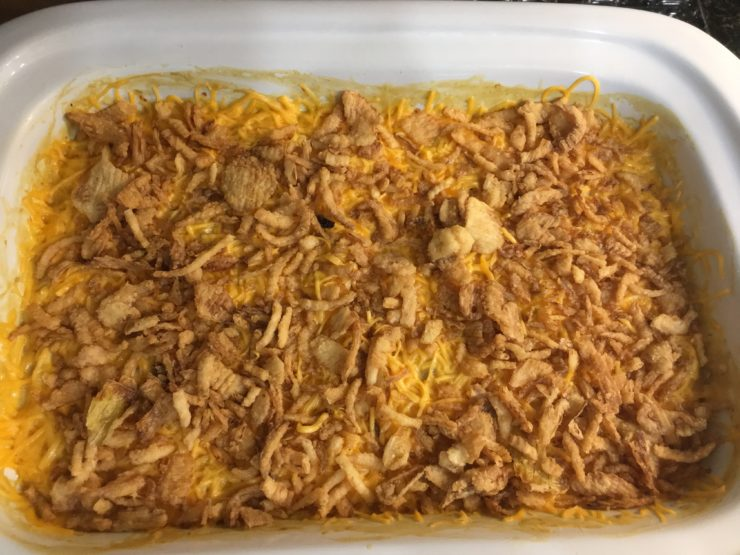 White casserole slow cooker with shredded chicken, macaroni noodles, mild tomatoes with green chilies, healthy cream of chicken soup, cream cheese, and onion soup mix inside. Casserole is topped with shredded, cheddar cheese and French fried onions.