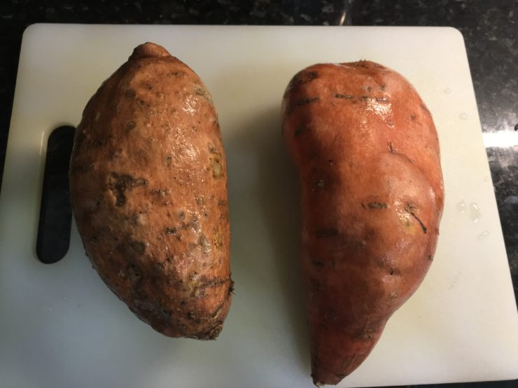 Two large sweet potatoes on a white cutting board.